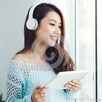 Free Asian Woman Enjoying View On Windowsill And Listening To Music. Stock Photo - 102804070