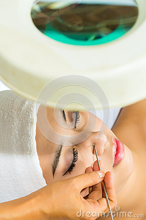 Asian woman getting a facial treatment in spa
