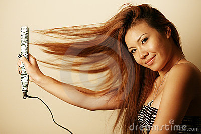 Asian woman with hair straightener