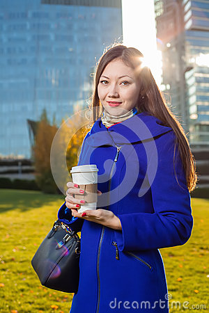 Free Asian Woman Holding Coffee In Hand, Standing Outdoors Behind Skyscrapers Stock Photo - 79953330