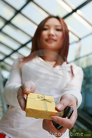 Asian woman holding gold gift box
