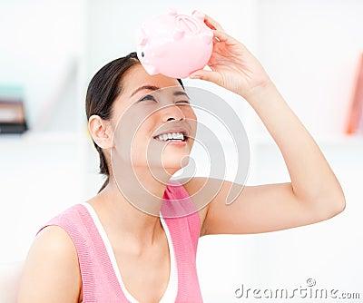 Asian woman looking through an empty piggy bank