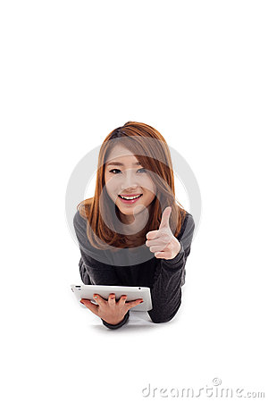 Asian woman lying down with tablet PC and showing thumb.