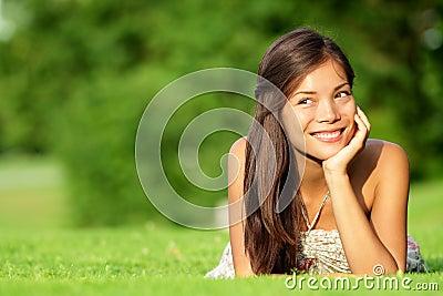 Asian woman lying in grass