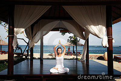 Asian Woman Meditating by the Beach