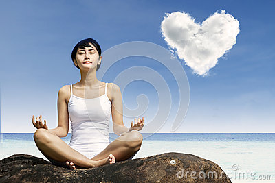Asian woman meditating at beach