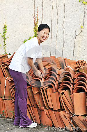 Asian woman move terracotta tiles
