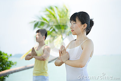 Asian woman performing yoga at the coast.