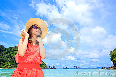 Asian woman in a pink dress standing on the beach