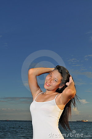 Asian woman posing by the beach styling her hair