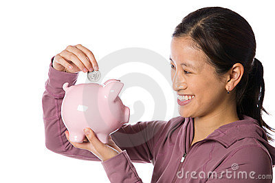 Asian woman putting money into a piggy bank