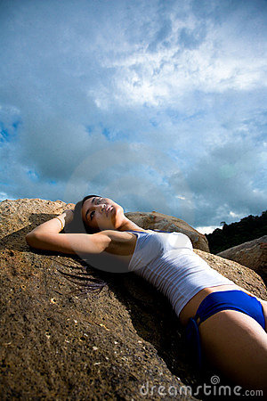 Asian woman relaxing on the rock