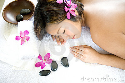 Asian woman restful on massage therapy bed