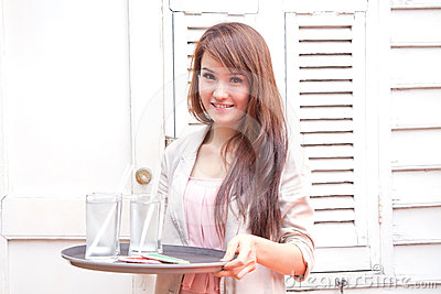 Asian woman serving a glass of water