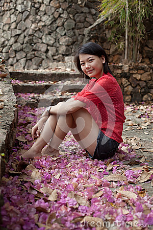Asian woman sitting on ground with paper flowers