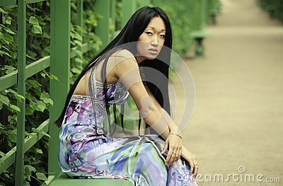 Asian woman sitting on the park bench