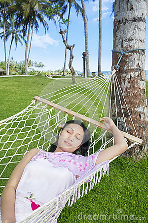 Asian woman sleep in hammock at beach