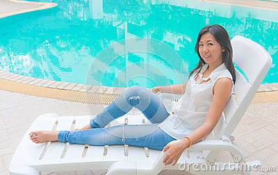 An Asian woman standing beside a swimming pool