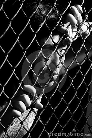 Asian woman staring fiercely through a fence