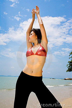 Asian woman stretching hands up on the beach