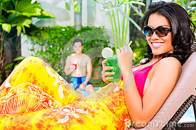 Asian woman tanning at pool with cocktail