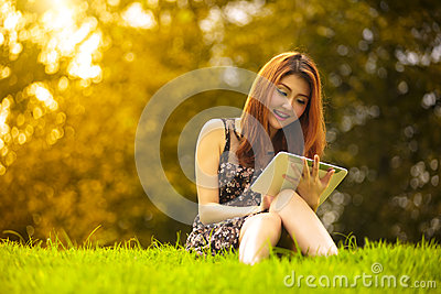 Asian woman using digital tablet in park