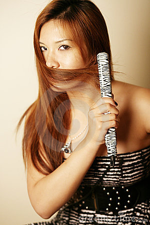 Asian woman using hair straightener