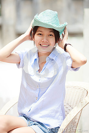Asian woman wearing a blue hat with smiling face