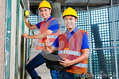 Asian worker controlling building on construction site