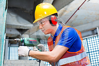 Asian worker drilling in construction site wall