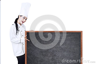 Beautiful chef pointing on copyspace