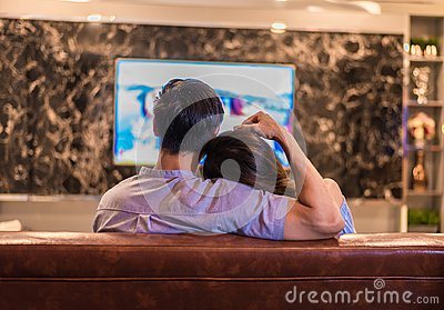 Asian young lovers watching television on sofa. Couples and Relax concept. Holiday and vacation concept. Night dating and Stock Photo
