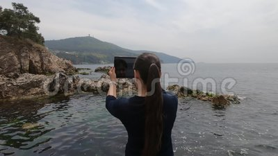Asiatisch-aussehendes touristisches Mädchen macht Fotos von Inseln, von Felsen und von Meer in der Türkei stock video
