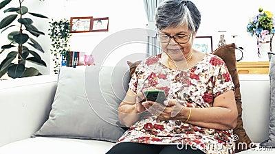 Asiatische ältere Frau, die zu Hause intelligentes Telefon, glückliche Großmutter mit Technologie in der Hand verwendet Zeitlupe  stock video footage