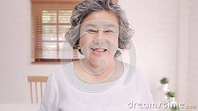 Asiatische ältere Frauen fühlen sich glücklich, lächeln und schauen auf die Kamera, während sie sich entspannen stock video footage