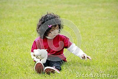 Asiatisches kleines Mädchen, das auf Gras spielt