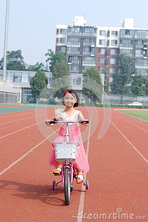 Asiatisches kleines Mädchen, das Fahrrad fährt