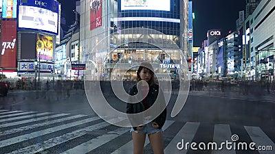 Asiatisches Mädchen Zeit Lapce, das an gedrängter Shibuya-Überfahrt, Tokyo, Japan aufwirft stock video