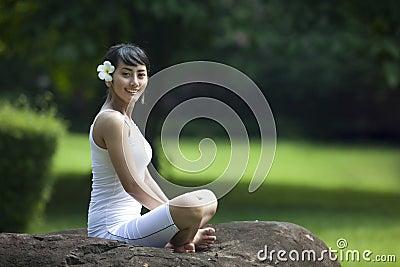 Asiatisk flicka som gör yoga som ser kameran