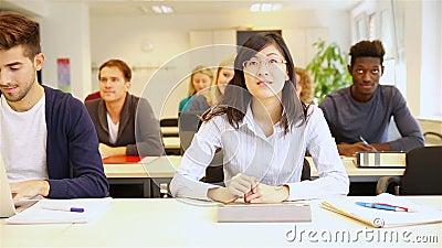 Asiatisk student som lyfter handen i klassrum
