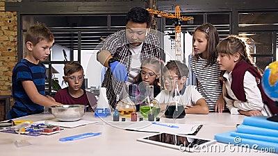 Asiatisk vetenskapslärare med barn i labbklass som arbetar med experiment genom att lägga torr is i kolvar med färgad vätska stock video