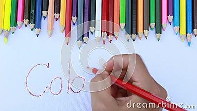 Asiatiska kvinnor som använder röd färg som skriver färgrikt ord under våg av färgblyertspennor i vitbok stock video
