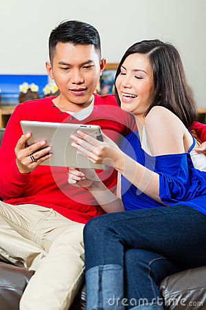Asiatiska par på soffan med en minnestavlaPC