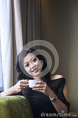 Asiatiskt kvinnligt drinkkaffe i lägenhet