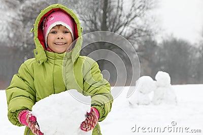 Asimiento de la muchacha en del terrón de las manos de la nieve