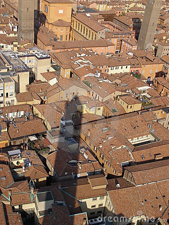 Asinelli tower shadow over Bologna red brick roofs