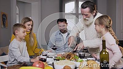 Aspetto un nonno di 60 anni con la barba e un bel tacchino arrosto per la sua famiglia che si riunisce intorno al tavolo da pranz video d archivio