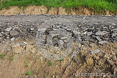 Asphalt debris on the soil where the grass.