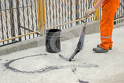 Asphalt worker apply tack coat (Bitumen Emulsion) with a broom.