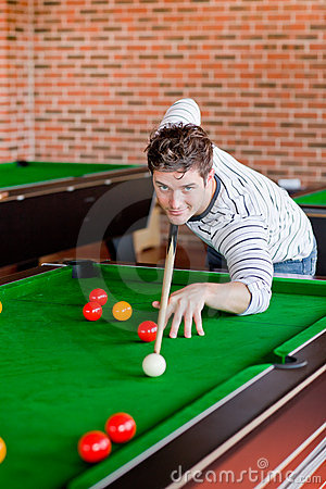 Assertive young man playing snooker